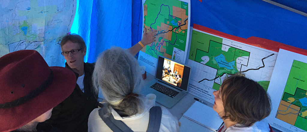 John Reid in Bowfest tent with people and maps